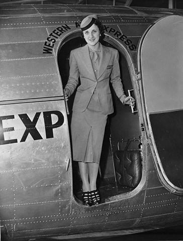 Elythe Loge standing in doorway of Douglas DC-3. Negative #WAL 12077. Job #7-20-11